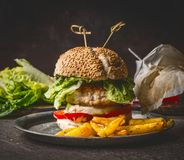 Homemade burger on dark rustic wooden background with French fries , front view, close up. Fast food. And snack concept Stock Photos