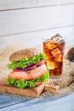 Homemade burger with fish served with cold drink Royalty Free Stock Image