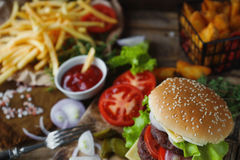 Homemade burger, fried potatoes, french fries,fast food set. Delicious homemade burger, fried potatoes, fresh tomatoes, lettuce, onions, cheese on rustic wooden Royalty Free Stock Photo