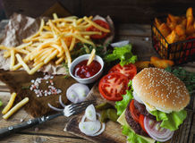 Homemade burger, fried potatoes, french fries,fast food set. Delicious homemade burger, fried potatoes, fresh tomatoes, lettuce, onions, cheese on rustic wooden Stock Photography