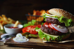 Homemade burger, fried potatoes, french fries,fast food set. Delicious homemade burger, fried potatoes, fresh tomatoes, lettuce, onions, cheese on rustic wooden Stock Photo