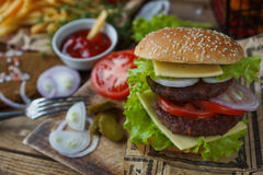 Homemade burger, fried potatoes, french fries,fast food set. Delicious homemade burger, fried potatoes, fresh tomatoes, lettuce, onions, cheese on rustic wooden Royalty Free Stock Photography