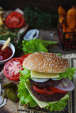 Homemade burger, fried potatoes, french fries,fast food set. Delicious homemade burger, fried potatoes, fresh tomatoes, lettuce, onions, cheese on rustic wooden Stock Images