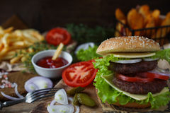 Homemade burger, fried potatoes, french fries,fast food set. Delicious homemade burger, fried potatoes, fresh tomatoes, lettuce, onions, cheese on rustic wooden Royalty Free Stock Image