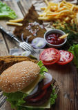 Homemade burger, fried potatoes, french fries,fast food set. Delicious homemade burger, fried potatoes, fresh tomatoes, lettuce, onions, cheese on rustic wooden Stock Image