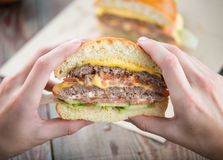Homemade Burger in the hands on wooden background stock photos