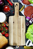 Homemade burger ingredients, beer and empty cutting board Stock Images