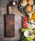 Homemade burger ingredients on kitchen table background with cutting board, top view Stock Photos