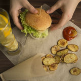 Homemade burger on a paper. Homemade Burger on paper with potatoes Stock Photo