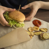 Homemade burger on a paper. Homemade Burger on paper with potatoes Royalty Free Stock Photo
