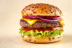 Homemade burger. Burger with tomato , lettuce , mayonnaise , cheese , onion , ketchup and flax seeds on bun , yellow wooden background Royalty Free Stock Photography