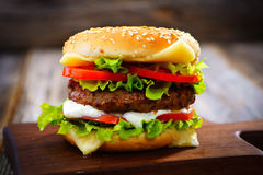 Burger. Homemade burger on  wooden background Stock Photos
