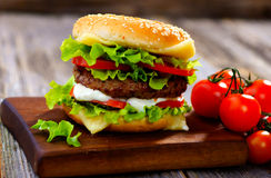 Burger. Homemade burger on  wooden background Royalty Free Stock Images