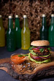Homemade burger on wooden serving board with lemonade, spicy tomato sauce, sea salt and herbs. Stock Photography