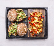 Homemade burgers with chicken in mustard sauce with arugula and garnish of ratatouille in a wooden box on wooden rustic background Royalty Free Stock Photos