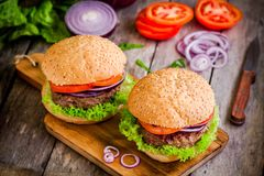 Homemade burgers with fresh organic vegetables on a rustic background Royalty Free Stock Photography