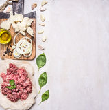 Homemade burgers, ground beef, herbs, oil and onion border ,place for text  wooden rustic background top view Stock Photos