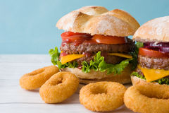 Homemade burgers and onion rings. Blue background Royalty Free Stock Photos