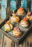 Homemade burgers in wooden tray over rustic table background Royalty Free Stock Image