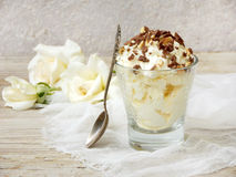 Homemade butter or lemon ice cream sprinkled with nuts and chocolate in a glass on a light wooden background. With white roses stock images