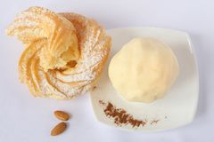 Homemade butter on a white porcelain plate, custard cake ring with icing sugar, almonds, grated cinnamon. White background stock photos