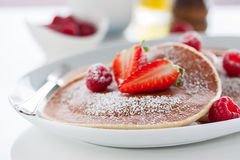 Homemade buttermilk american pancakes with fresh strawberry and raspberry on a white plate. On a white table for breakfast, closeup, selective focus Stock Photography