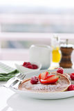Homemade buttermilk american pancakes with fresh strawberry and raspberry on a white plate. On a white table for breakfast, closeup, selective focus Stock Image