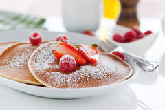 Homemade buttermilk american pancakes with fresh strawberry and raspberry on a white plate. On a white table for breakfast, closeup, selective focus Stock Photo
