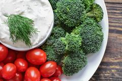 Homemade Ranch Dressing with Dill and Fresh Broccoli and Tomatoes. Homemade buttermilk ranch salad dressing with dill served with fresh cherry tomatoes and stock photography