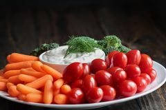 Ranch Dressing with Dill and Fresh Vegetables. Homemade buttermilk ranch salad dressing with dill served with fresh vegetables, cherry tomatoes, baby carrots and stock image