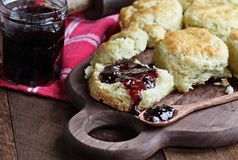 Homemade Buttermilk Southern Biscuits with Berry Fruit Preserves. Buttermilk southern biscuits or scones served with homemade fruit preserves. Top view stock photography