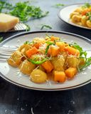 Homemade Butternut squash gnocchi with wild rocket and parmesan cheese.  Royalty Free Stock Image