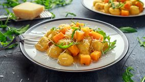 Homemade Butternut squash gnocchi with wild rocket and parmesan cheese.  Stock Photo