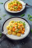 Homemade Butternut squash gnocchi with wild rocket and parmesan cheese.  Stock Image