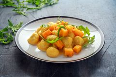 Homemade Butternut squash gnocchi with wild rocket in a plate.  Stock Photos
