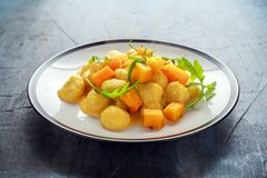 Homemade Butternut squash gnocchi with wild rocket in a plate.  Royalty Free Stock Photos