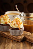 Homemade butterscotch cupcakes. With caramel syrup and cream cheese frosting royalty free stock photo