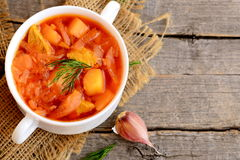 Homemade cabbage soup with meat and vegetables in a bowl, garlic on old wooden background. Dinner or lunch menu recipe. Closeup Stock Images
