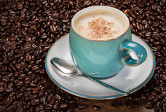 Homemade Cafe Latte. Homemade Cafe Late in a blue cup amongst fresh unground beans stock photography