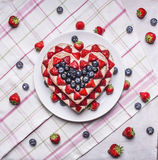 Homemade cake In the form of heart  with blueberries and strawberries On a white plate a background of a striped pink napkins w Royalty Free Stock Photo
