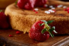 Homemade cake with fresh organic strawberries on cutting board over wooden background, shallow depth of field.