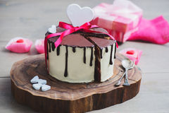 Homemade cake with hearts. Homemade cake with heart shaped decoration on a wooden board Royalty Free Stock Image