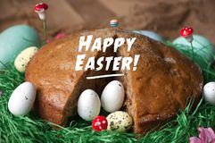 Homemade cake in a nest from fake green grass and Easter eggs isolated on sackcloth texture. Happy Easter CardBeautiful bouquet of royalty free stock image