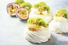Homemade cake Pavlova with whipped cream, fresh kiwi and passion fruit. Royalty Free Stock Photography