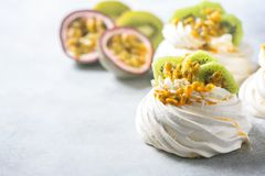 Homemade cake Pavlova with whipped cream, fresh kiwi and passion fruit. Royalty Free Stock Images