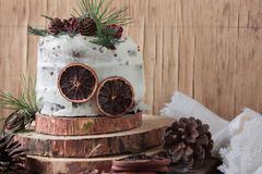 A piece of homemade cake with persimmon decorated with frosting cream cheese and sprinkled with chocolate in the New Year decorati Stock Images