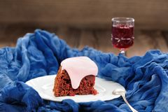 Homemade cake with pink icing and wine on blue background Royalty Free Stock Image