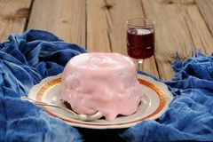 Homemade cake with pink icing and wine on blue background Stock Image