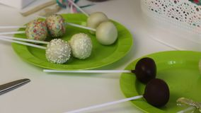 Homemade cake pops lie on the plates before packing. Candy covered with black and white chocolate. With various topping. Nearby ar. E gift boxes for packaging stock footage