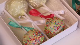 Homemade cake pops packed in gift boxes. Candy covered with black and white chocolate. Decorated with a different color dressing. Homemade cake pops packed in stock video footage
